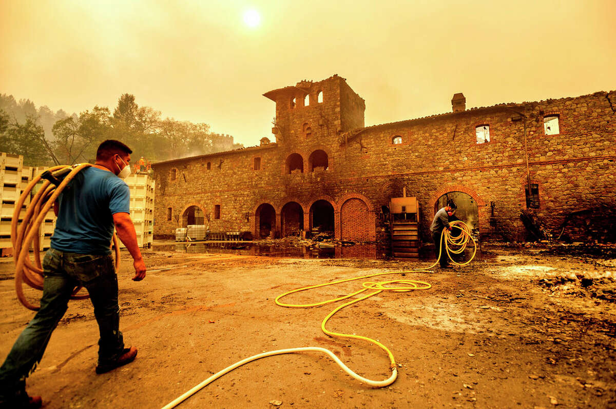 Winery workers Carlos Perez, left, and Jose Juan Perez extinguish hotspots at Castello di Amorosa, Monday, Sept. 28, 2020, in Calistoga, Calif., which was damaged in the Glass Fire.