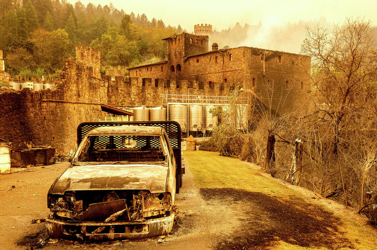 A damaged vehicle and wine warehouse stand, Monday, Sept. 28, 2020, in Calistoga, Calif., at Castello di Amorosa, which was damaged in the Glass Fire.