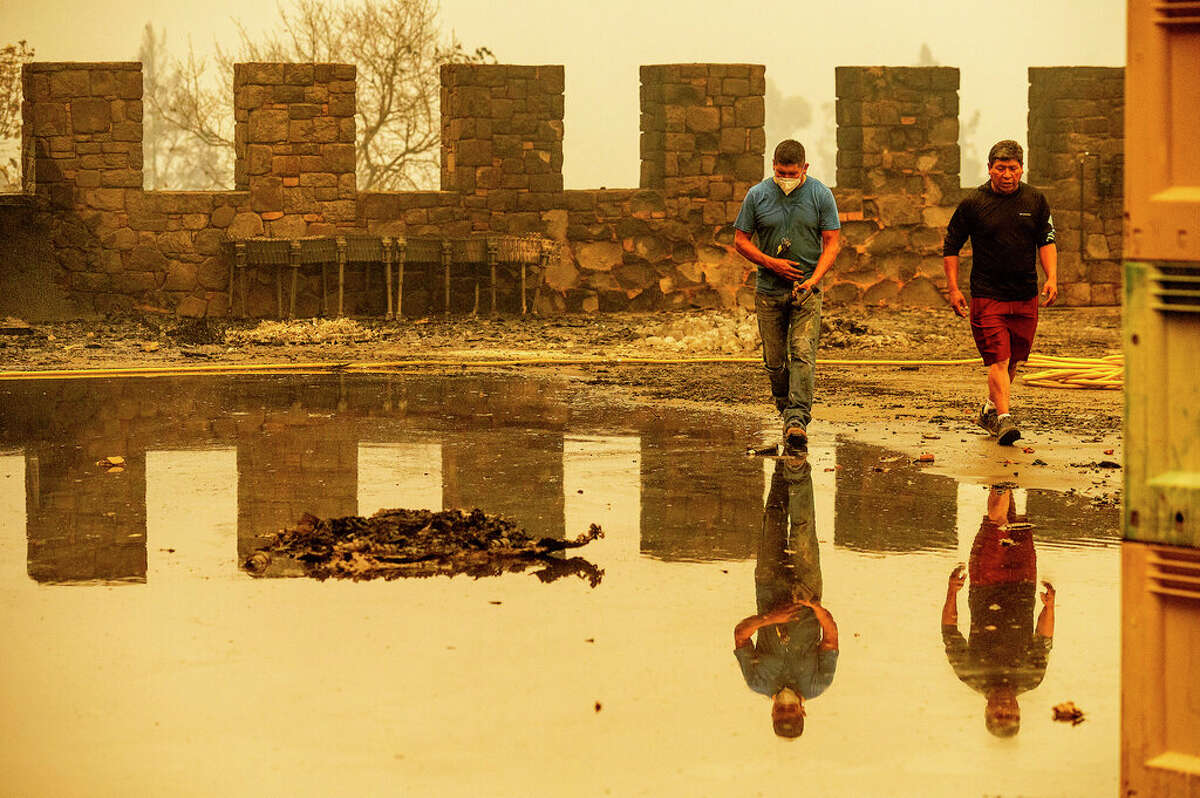 Winery worker Carlos Perez, left, walks, Monday, Sept. 28, 2020, in Calistoga, Calif., through Castello di Amorosa, which was damaged in the Glass Fire. Perez helped build the wine cellar that was scorched in the blaze.