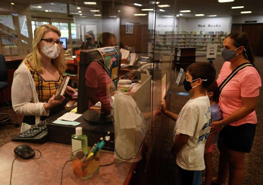 Emily Boyle, son Matthew, 10, and daughter Catherine, 7, check out books on the first day of reopening at the Trumbull Library in Trumbull, Conn. on Monday, September 28, 2020. Photo: Brian A. Pounds / Hearst Connecticut Media / Connecticut Post