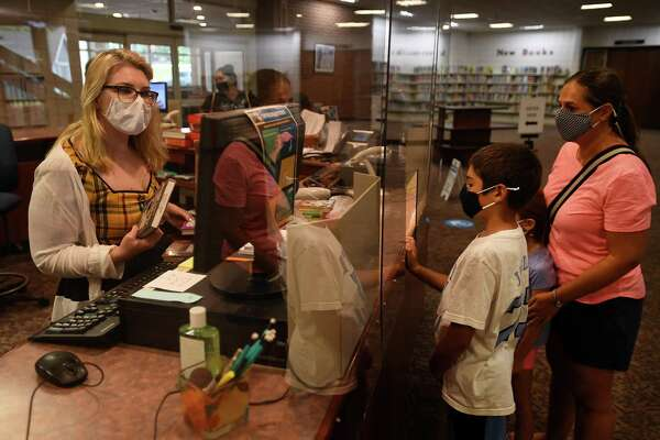 Emily Boyle, son Matthew, 10, and daughter Catherine, 7, check out books on the first day of reopening at the Trumbull Library in Trumbull, Conn. on Monday, September 28, 2020.