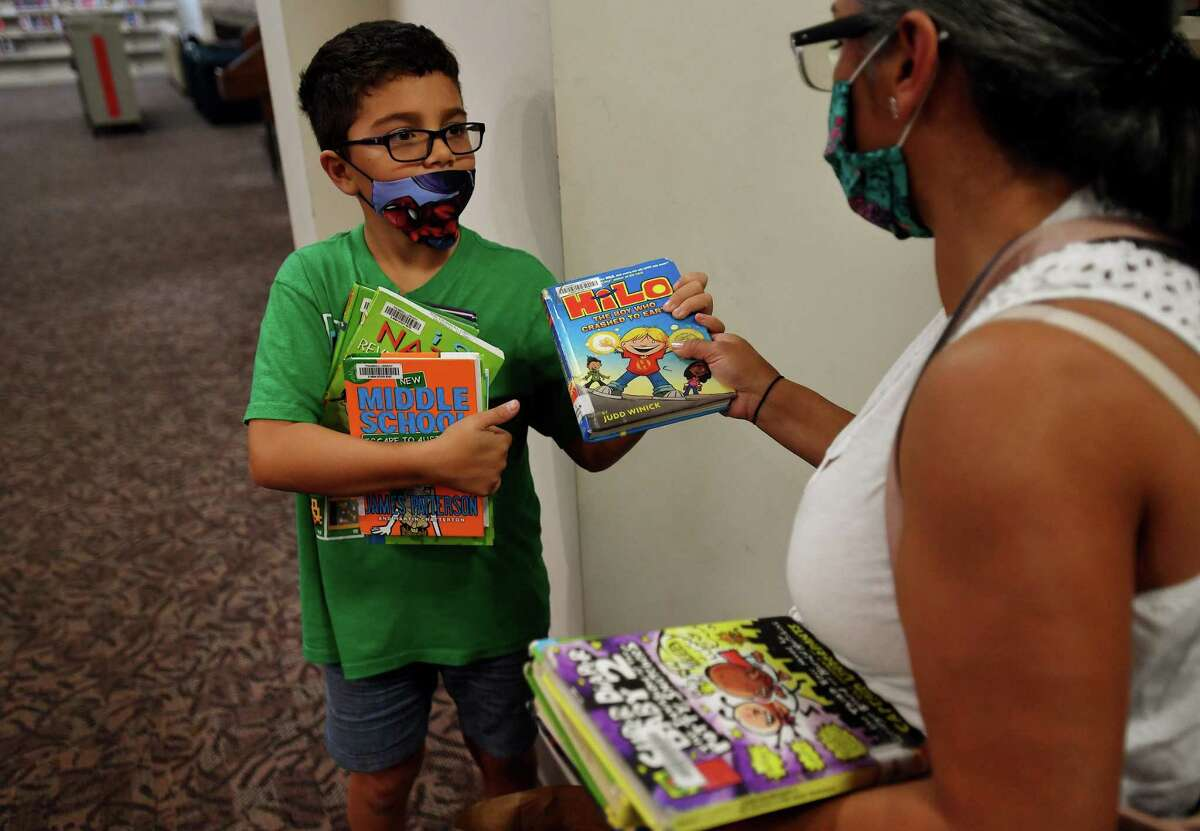 Dylan Rorick, 9, and his mom Glenda pick out books on the first day of reopening at the Trumbull Library in Trumbull, Conn. on Monday, September 28, 2020.