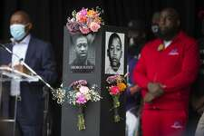 A photo of George Floyd is shown on a pillar as Mayor Sylvester Turner speaks during the opening of the Say Their Names Memorial in Emancipation Park on Monday, Sept. 28, 2020 in Houston. Brought to Houston by rap artist and activist Trae Tha Truth and Say Their Names, the memorial is dedicated to those who have lost their lives due to racial injustice. More than 200 photos, including George Floyd, Breonna Taylor, Dr. Martin Luther King, Jr., and Emmett Till to name a few, are featured in the walk of black pillars with photos on each side. The traveling memorial will be installed at the park for 15 days.