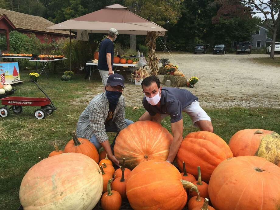 Gregg Chann and Vince DiLullo of the Wilton Kiwanis Pumpkin Committee, review the wide assortment of pumpkins they have for sale this year, including some that weigh around 100 pounds. Photo: Patricia Gay/Hearst Connecticut Media