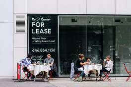 Diners eat outside a French restaurant in front of a storefront for lease in New York.