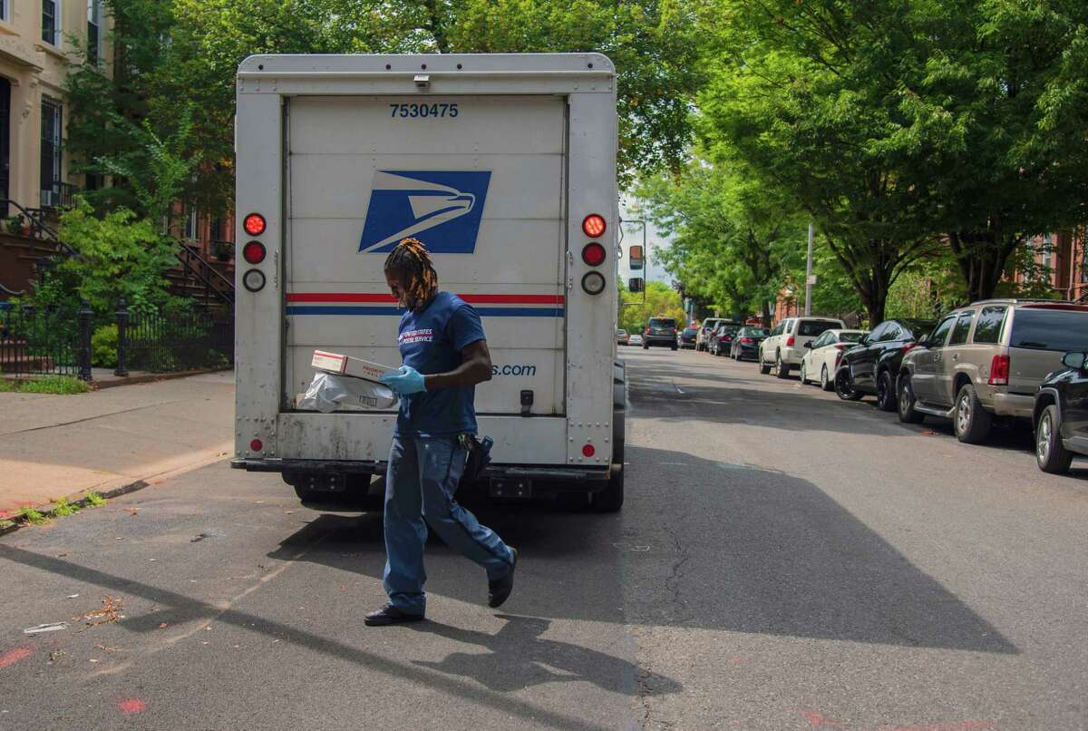 A postal worker delivers packages in Brooklyn on Sept. 10, 2020.