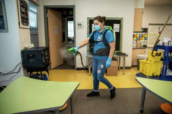 A worker operates an electrostatic machine to clean a classroom at an elementary school in Leander, Texas, on Sept. 18, 2020.