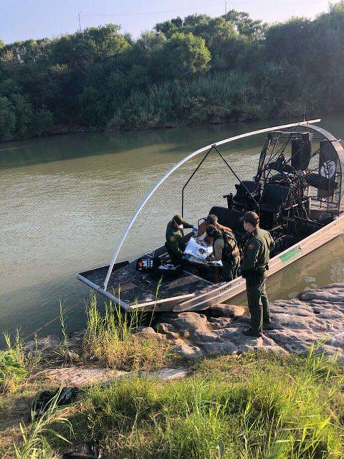 U.S. Border Patrol agents are seen rendering aid to an immigrant who almost drowned in the Rio Grande near downtown Laredo on Saturday. Photo: Courtesy Photo /U.S. Border Patrol