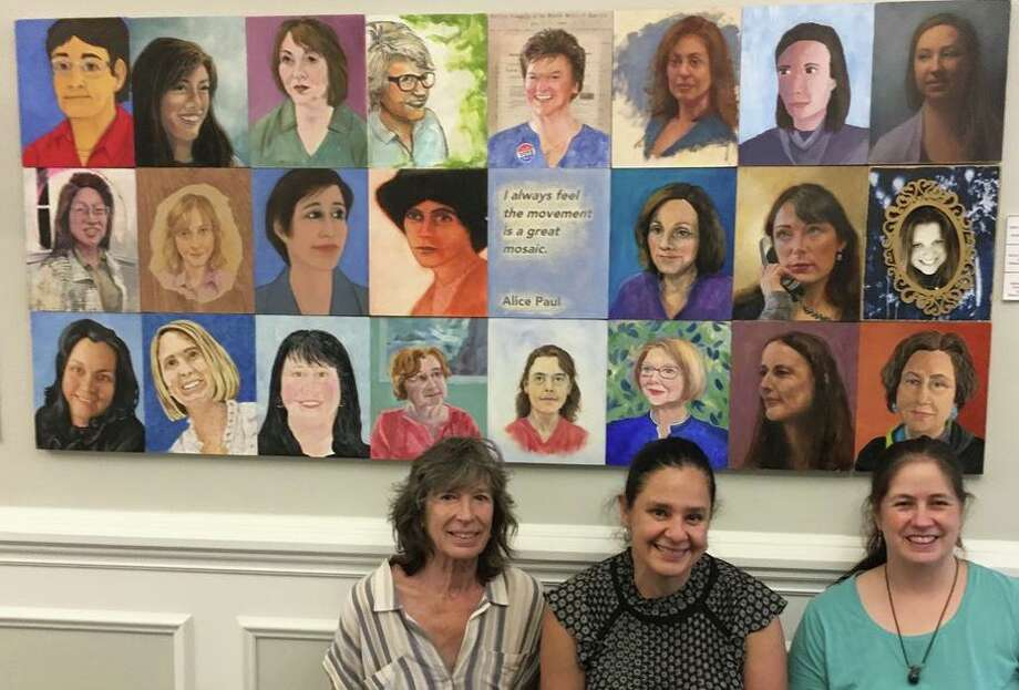 Holly Hawthorn, Lenor Dao and ShawnaLee Kwashnak hung the portraits of town hall women in the front of town hall. Photo: Contributed Photo