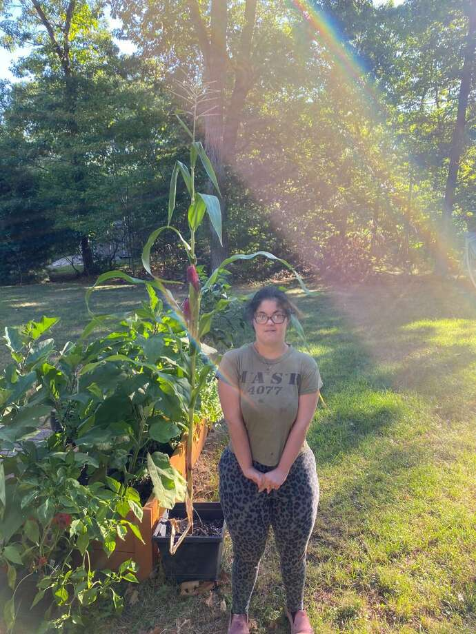 Johanna Vecchione attends the Maggie Daly Arts Cooperative, (MDAC), the non-working/artistic side of The Kennedy Center. When COVID-19 struck back in March, classes were put on hold. The Kennedy Center and MDAC got together and created a virtual program which included a gardening class, where Johanna is shown next to a plant with emerging ears of corn. Photo: Contributed Photo /