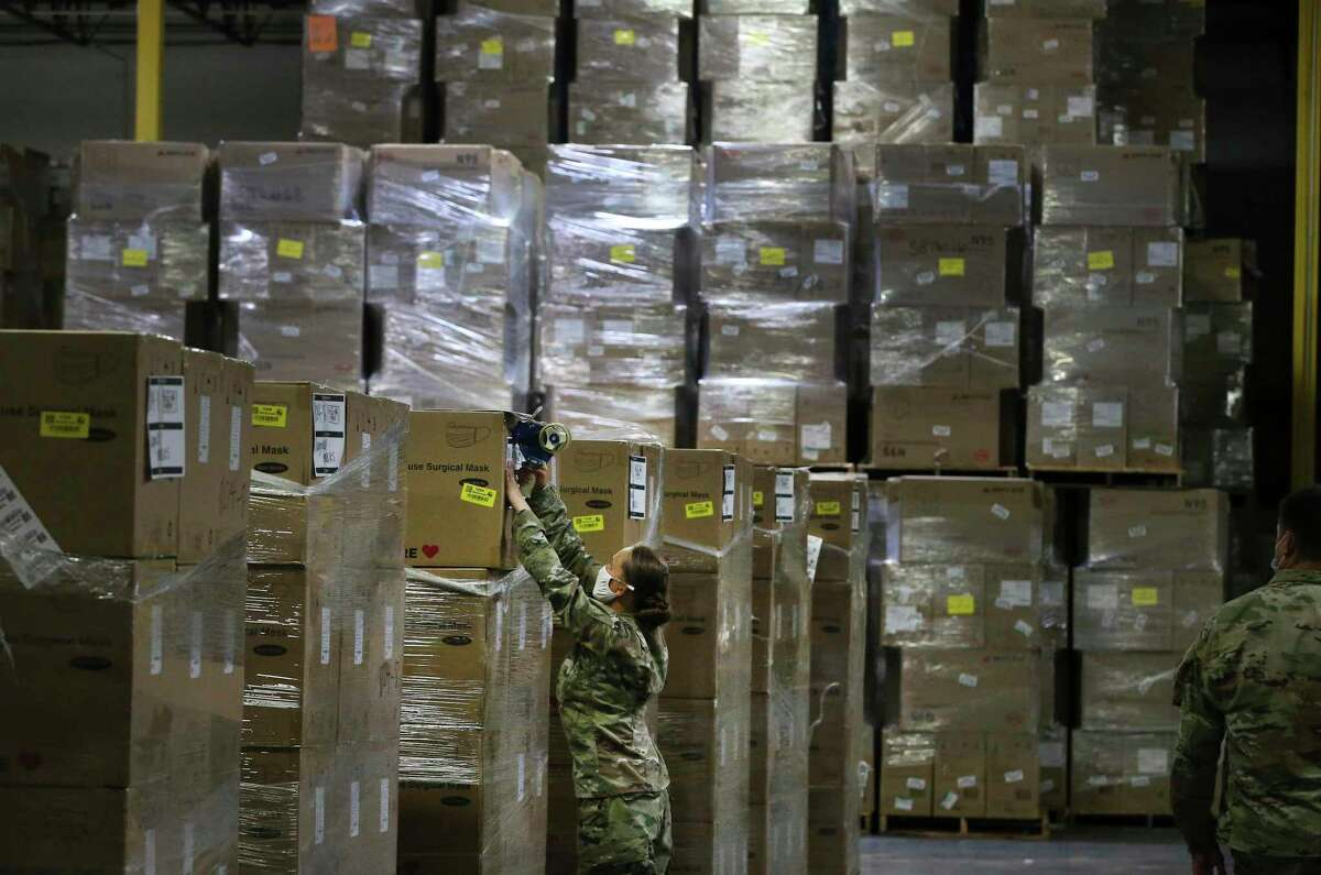 A Texas National Guard personnel works with boxes of Personal Protective Equipment as Texas Gov. Greg Abbott along with state officials visit a Texas Division of Emergency Management Warehouse located within the city on Aug. 4. Abbott toured the facility which is one of 40 warehouses in the state that stores and distributes the PPE equipment. Units of Texas National Guard are deployed throughout the state to help with the Coronavirus pandemic.