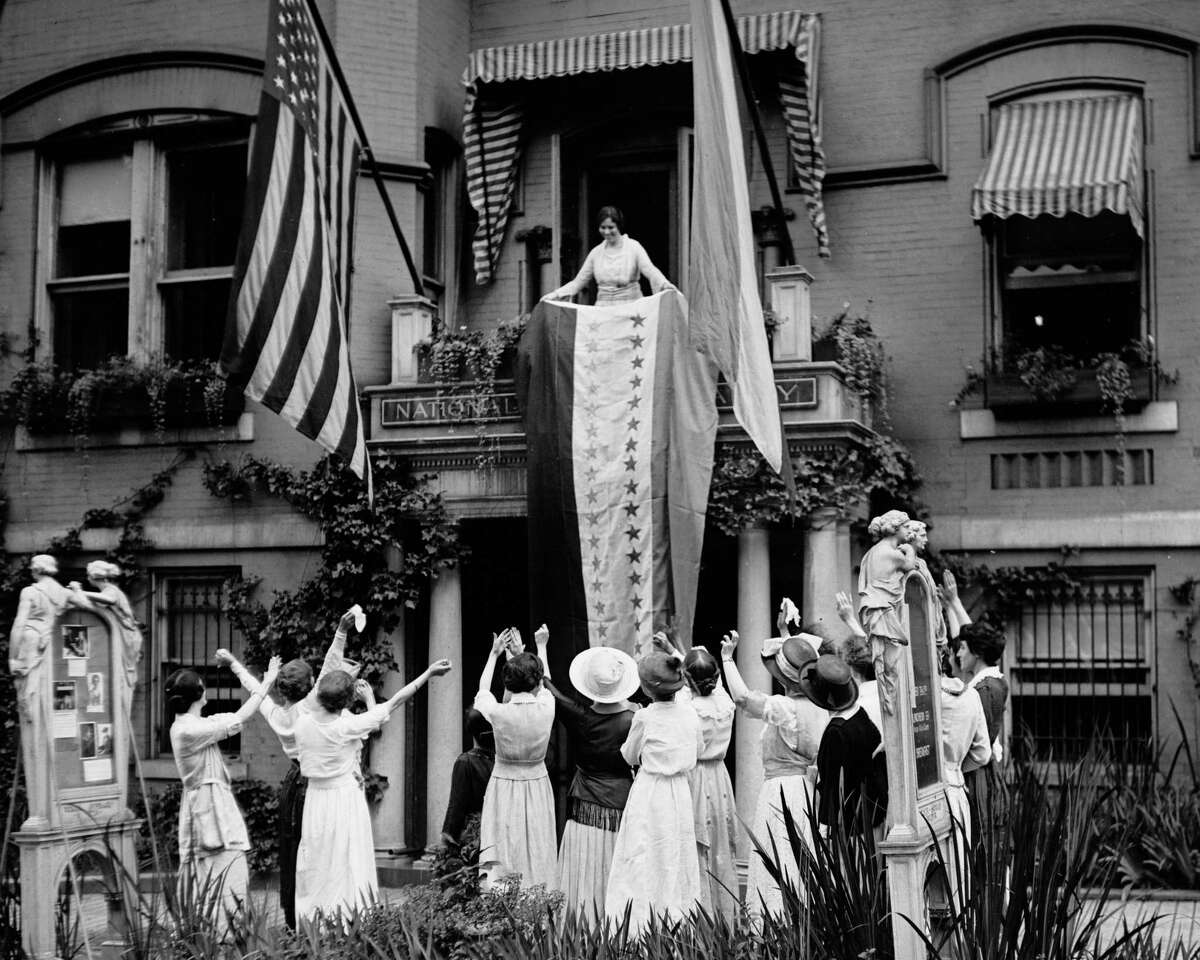 In this Aug. 19, 1920 photo made available by the Library of Congress, Alice Paul, chair of the National Woman's Party, unfurls a banner after the ratification of the 19th Amendment, at the NWP's headquarters in Washington.