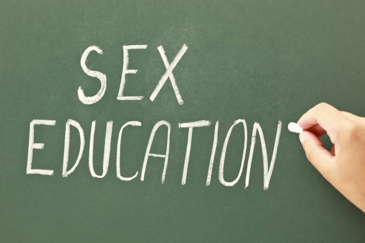 Hand writing sex education on a green blackboard with a chalk. This is an exclusive image and it can only be found in iStockphoto.