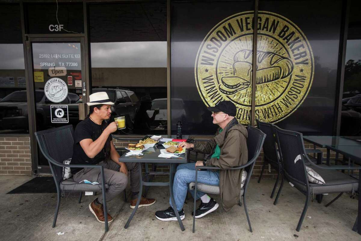 Desmond Chan, left, and Charles Frey enjoy lunch outside on the patio at Wisdom Vegan Bakery.