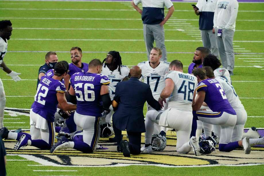 Tennessee Titans and the Minnesota Vikings players meet at midfield following an NFL football game, Sunday, Sept. 27, 2020, in Minneapolis. Tennessee won 31-30. The NFL says the Tennessee Titans and Minnesota Vikings are suspending in-person activities after the Titans had three players test positive for the coronavirus, along with five other personnel. The league says both clubs are working closely with the NFL and the players' union on tracing contacts, more testing and monitoring developments. The Titans are scheduled to host the Pittsburgh Steelers on Sunday.(AP Photo/Jim Mone) Photo: Jim Mone, Associated Press / Copyright 2020 The Associated Press. All rights reserved