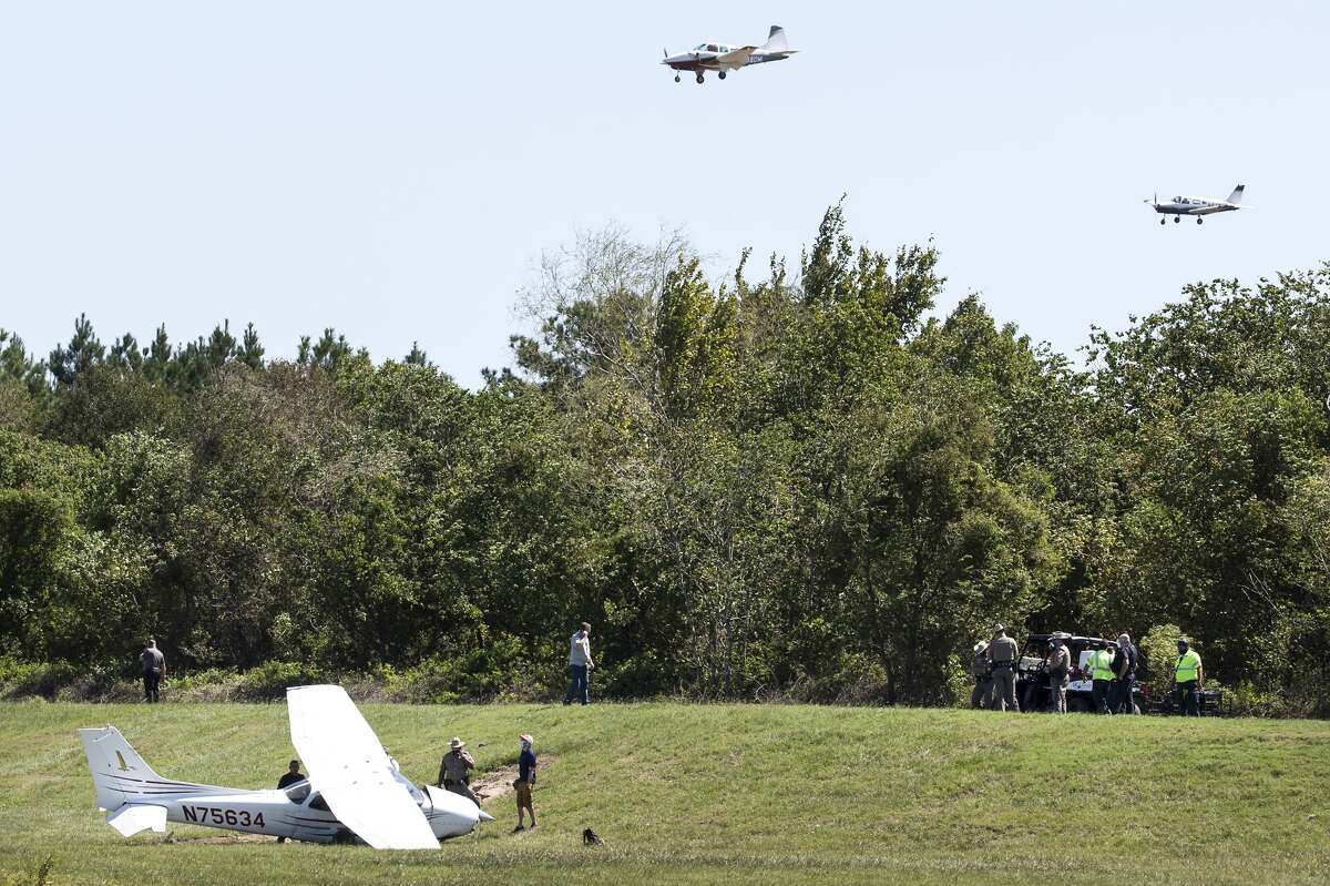 Officials investigate the scene of a light plane crash just off the runway at Hooks Airport on Tuesday, Sept. 29, 2020 in Tomball.