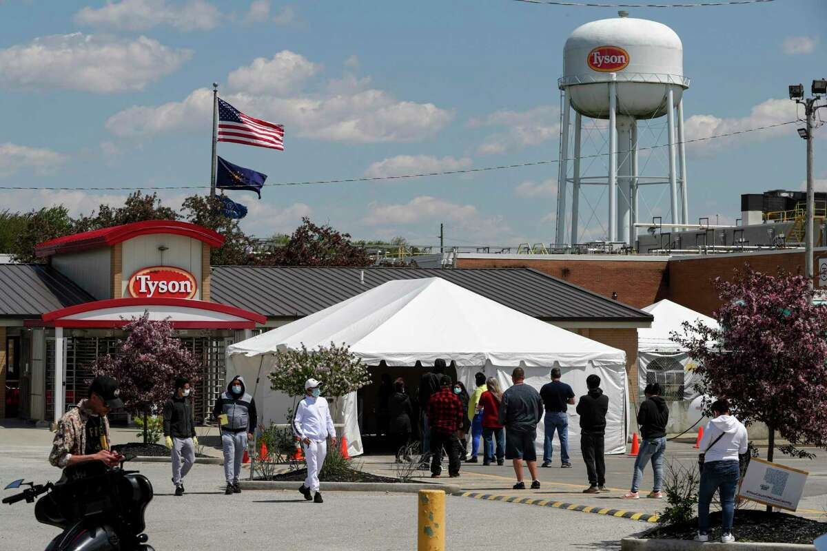 Workers line up to enter the Tyson Foods pork processing plant in Logansport, Ind., Thursday, May 7, 2020. In Cass County, home to the Tyson plant, confirmed coronavirus cases have surpassed 1,500. That's given the county - home to about 38,000 residents - one of the nation's highest per-capita infection rates. (AP Photo/Michael Conroy)