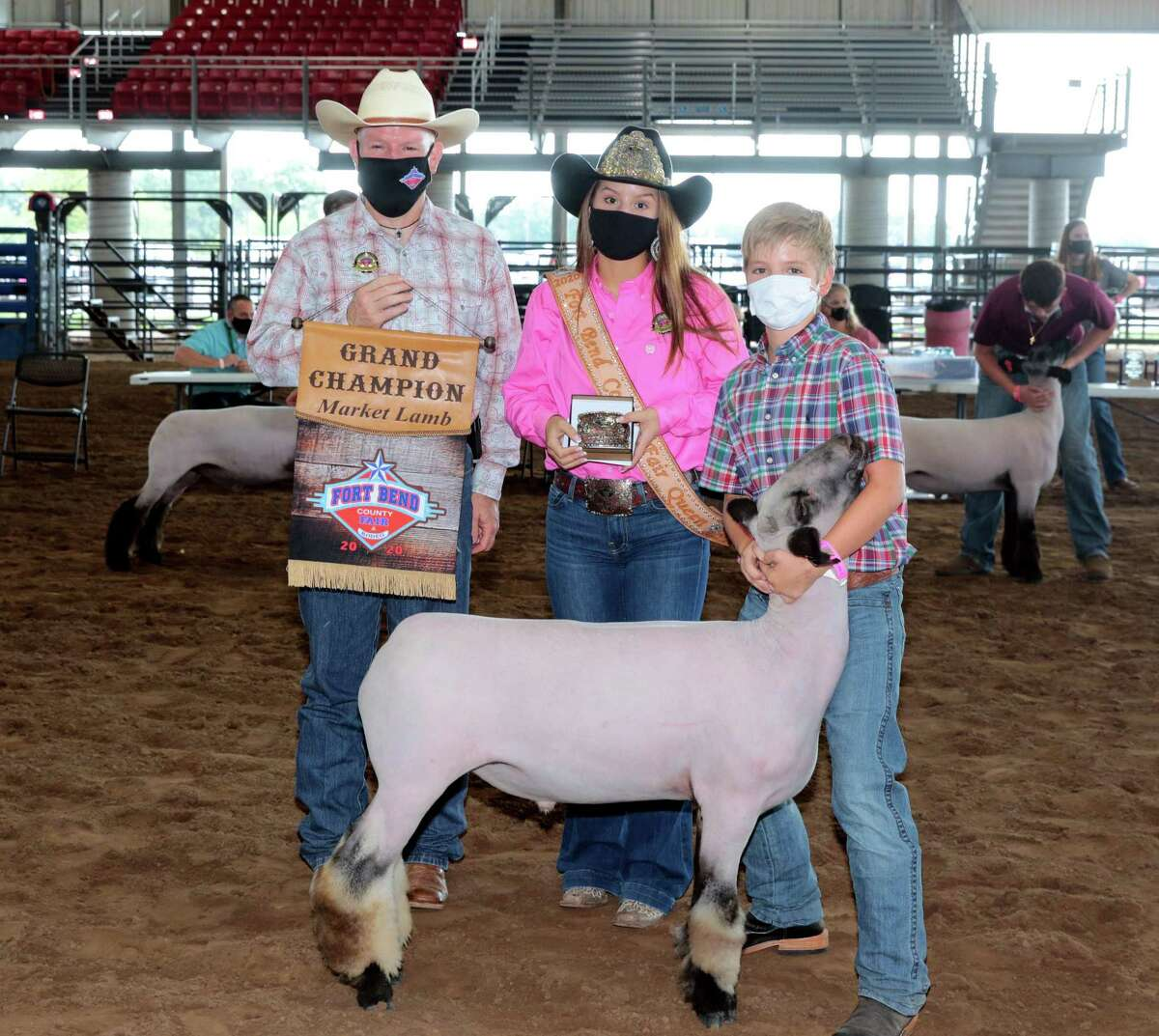 Fort Bend County Fair and Rodeo President Sean Gutierrez (left), 2020 Fort Bend County Fair Queen Caroline O'Driscoll presenting Grand Champion Lamb buckle and banner to Zane Atkinson.
