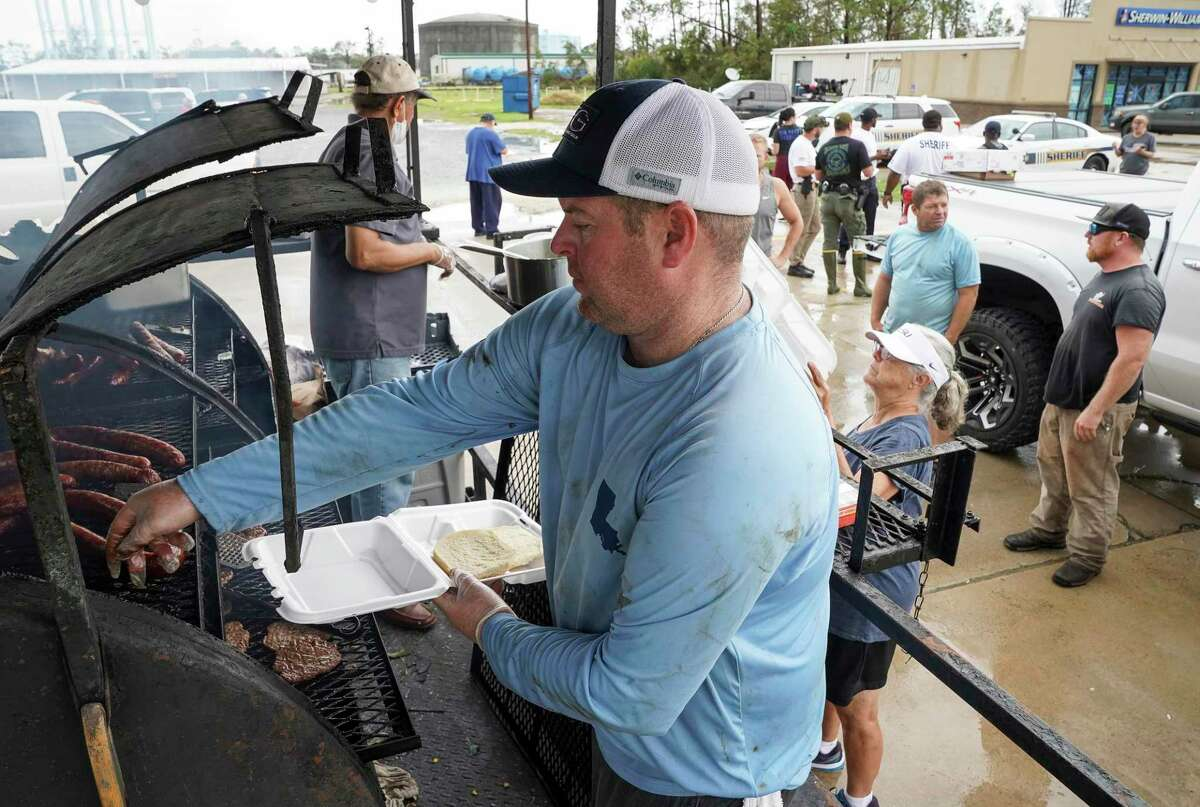 Michael Boyer prepares a plate of food for people coming by the BBQ pit he setup in the parking lot of Nina-P's Cafe on Friday, Aug. 28, 2020, in Lake Charles, La. Boyer, who lives in Westlake, made some calls to borrow the BBQ pit to be able to feed people with food he also got restaurants to donate.