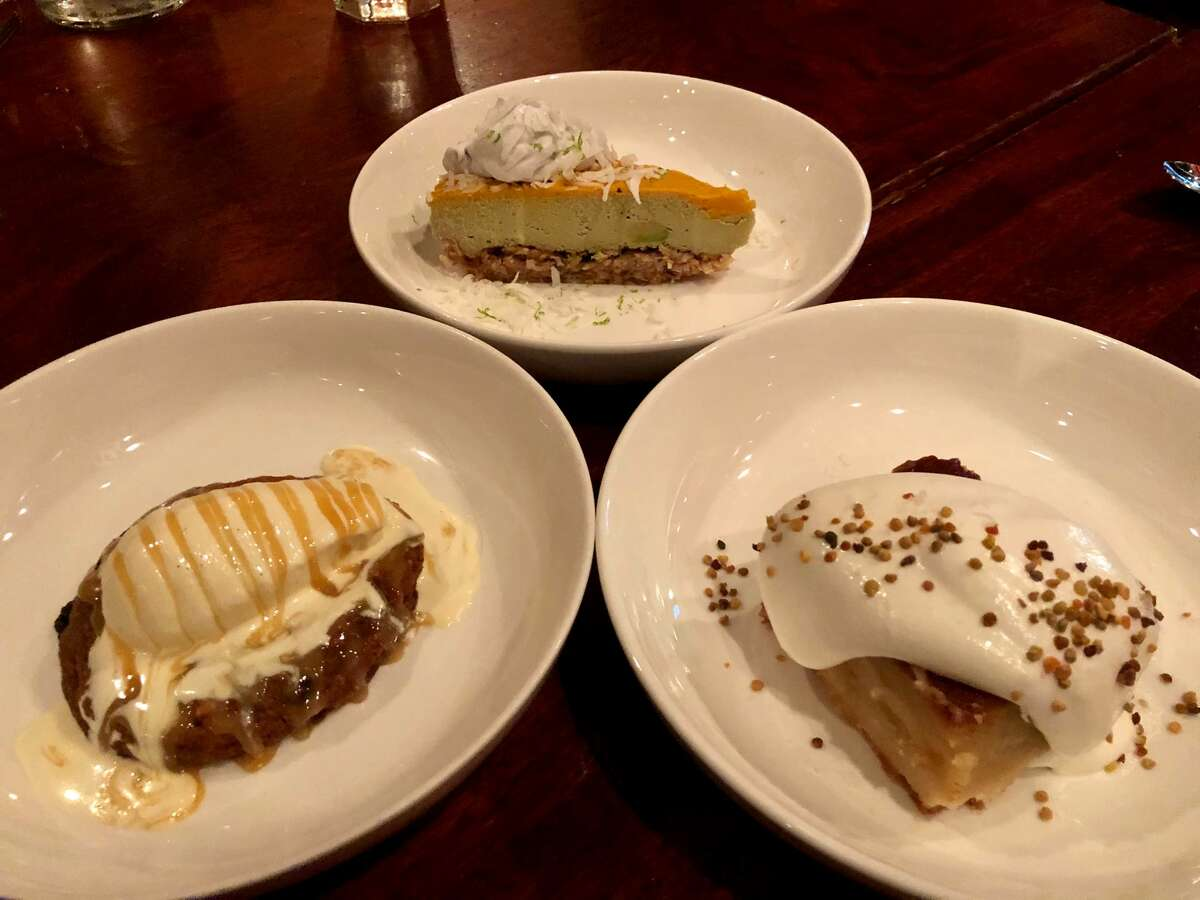 Desserts at at New World Bistro Bar in Albany, clockwise from top: avocado-lime semifreddo with coconut, salted honey pie and oversize chocolate cookie. (Photo by Susie Davidson Powell for the Times Union.)