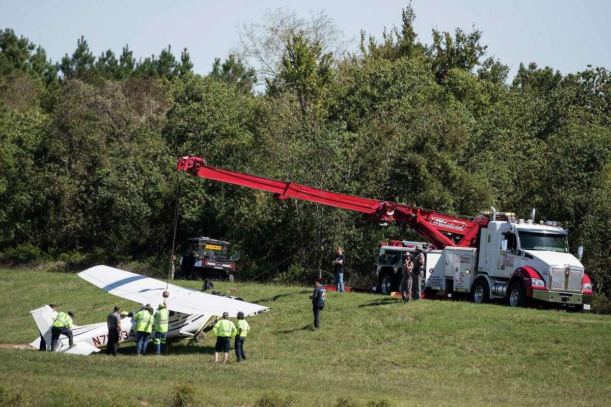 Officials investigate the scene of a light plane crash just off the runway at Hooks Airport on Tuesday, Sept. 29, 2020 in Tomball. A student pilot running flight patterns crashed Tuesday into an empty retention pond outside Hooks Airport, Texas Department of Public Safety troopers said. The pilot, who was not injured, lost control of the rudder of the Cessna 172 aircraft and crashed in the pond behind a subdivision, Sgt. Richard Standifer said. The pilot was not injured. The plane belonged to a flight school, of which the pilot was a student, Standifer said. Planes continued to take off and land at the Tomball area airport as authorities investigated the crash. The airport is about 23 miles north of Houston.