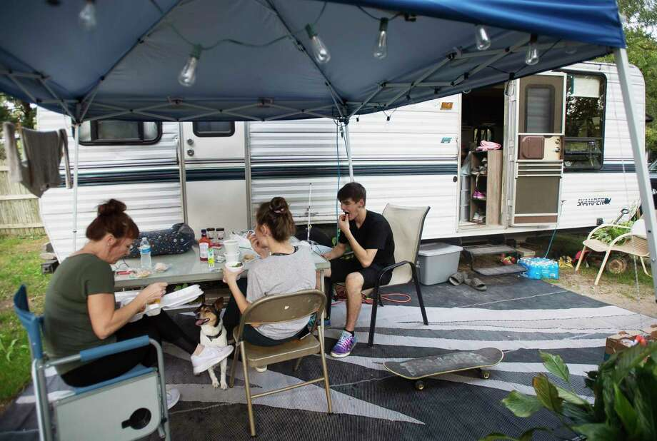 From left, Sanford resident Rebecca Johnson, her daughter Autumn, and Julian Plamp, Autumn's boyfriend, eat dinner together Thursday outside of the RV Rebecca and Autumn are living in on their property as renovation work continues on their home. They will be featured in a special report in Saturday's Midland Daily News. (Katy Kildee/kkildee@mdn.net)