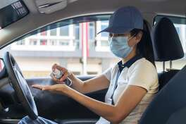 cautious woman wearing a protective mask spraying anti-bacterial sanitizer spray on hand inside a car, after the lockdown from covid-19 pandemic