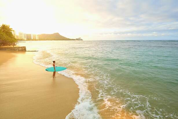 Pacific Islander woman holding surfboard on beach.