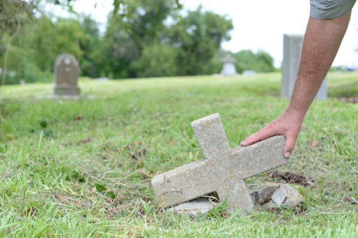 A volunteer recovers part of a grave marker at Crown Hill Cemetery in this 2016 photo. The cemetery, 813 N. Richey, will host