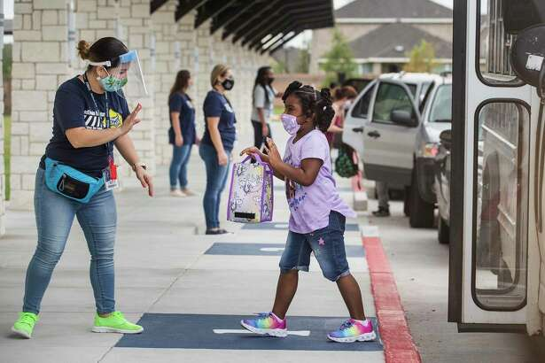 Miriam Vences welcomes students in the car rider line for their first day of in-person school at McElwain Elementary School on Tuesday, Sept. 8, in Katy. A little less than half of Katy ISD's students will return to their classrooms for in-person instruction this week. The remainder of the districts students will to to school remotely, due to coronavirus precautions.