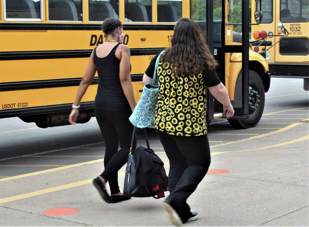 Woodrow Wilson Middle School students who attended in-person classes Tuesday afternoon board their buses at the 1 Wilderman's Way facility in Middletown.