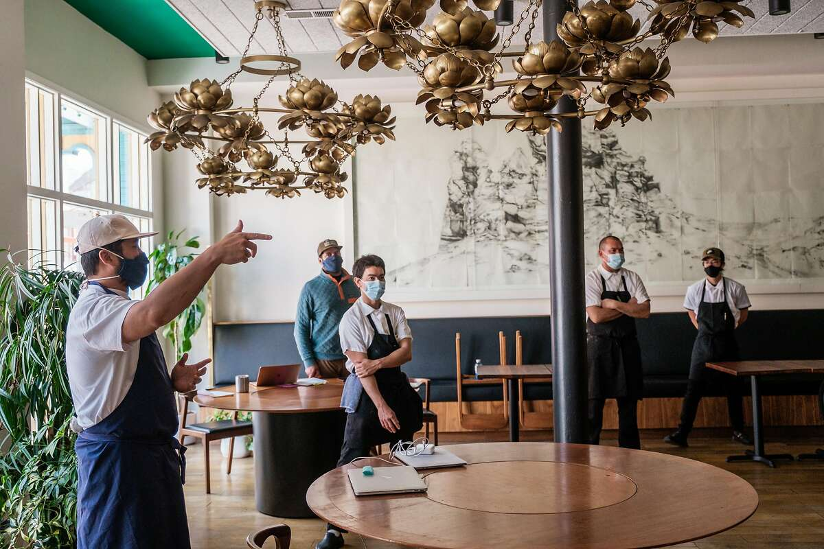 Brandon Jew (left), owner of the restaurant Mister Jiu's, speaks to his staff regarding indoor dining Sept. 18, after Mayor London Breed announced that San Francisco restaurants would be allowed to welcome diners inside as soon as the end of the month.