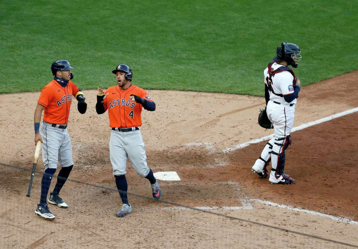 The Astros' Carlos Correa (left) and George Springer celebrate after scoring on Michael Brantley's ninth-inning single during their Game 1 victory over the Twins on Tuesday at Target Field in Minneapolis.