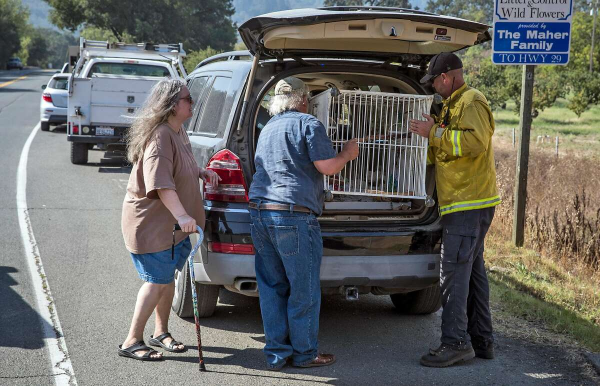 Battalion Chief Gino DeGraffenreid, right, helps Lynn Boro and Cio Perez load Lynn's parrot cage into his car after they evacuated her home and couldn't bring the cage with them as the Glass fire burned north of St. Helena, Calif., on Sunday, September 27, 2020.