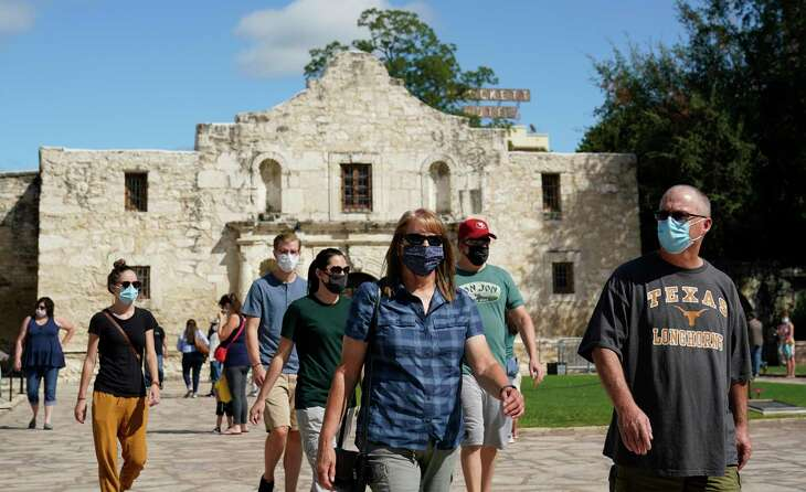 Visitors wearing masks for protection from COVID-19 leave the recently reopened Alamo, Tuesday, Sept. 22, 2020, in San Antonio. The Texas Historical Commission is set to decide whether to allow the restoration and relocation of the Cenotaph, a 1930s-era stone monument to Texas revolutionaries killed in the Battle of the Alamo, as part of an effort to reclaim the historical footprint of the Alamo as part of a redevelopment plan. (AP Photo/Eric Gay)