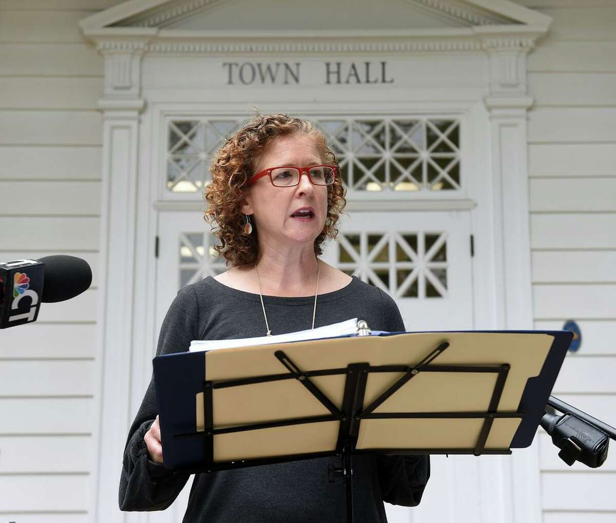 In this file photo, Erin Boggs, executive director of Open Communities Alliance, speaks in front of Woodbridge Town Hall on Sept. 29, 2020 concerning the organization's challenge to the town's zoning laws restricting multi-family developments of 3 or more units.