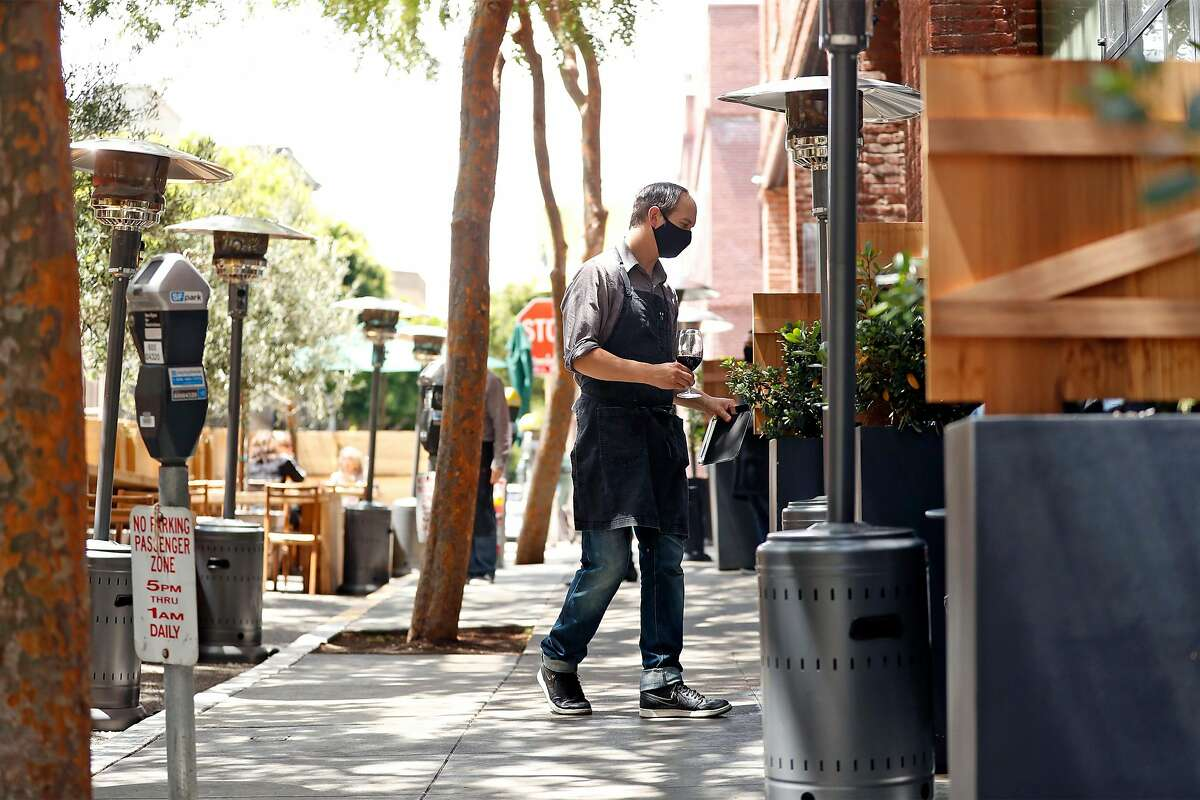 Cotogna server Michael Kudra delivers a glass of wine to a diner at the restaurant's parklet in San Francisco's Jackson Square in July. The city is waiving permit fees for the temporary sidewalk structures through 2022.
