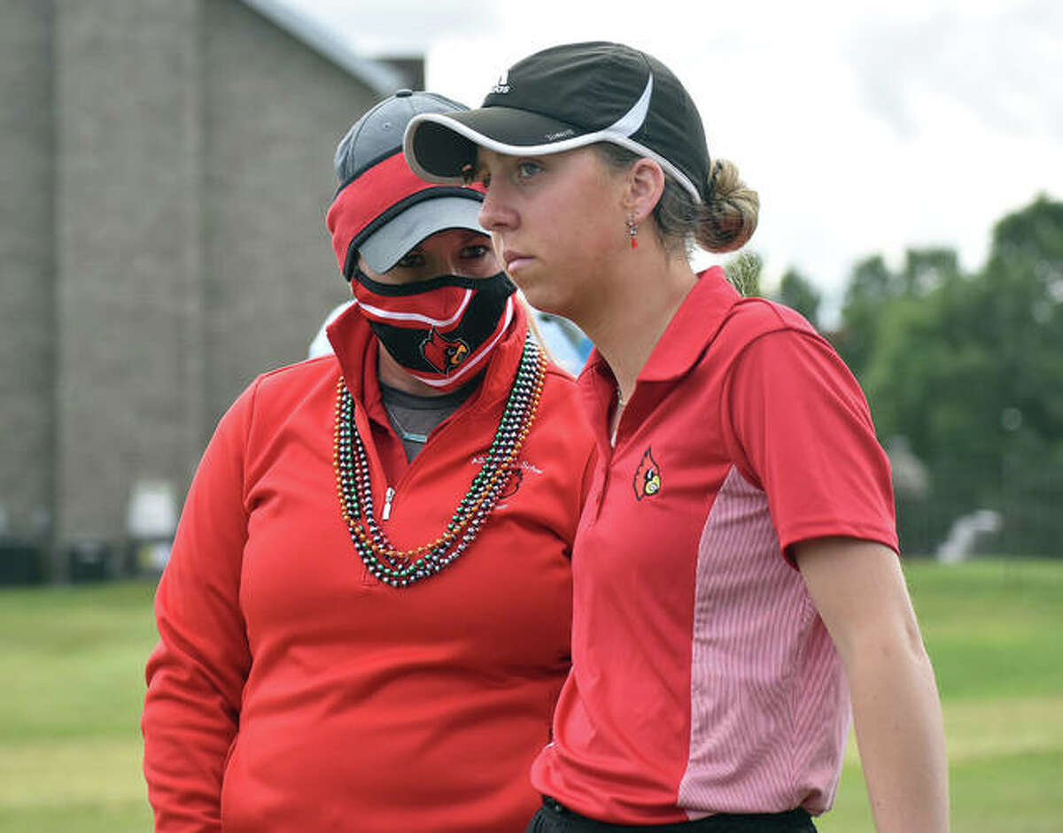 Alton senior Natalie Messinger (right) consults with Redbirds coach Carey Cappel before teeing off on the first hole Tuesday at the SWC Tourney at Far Oaks golf course in Caseyville.