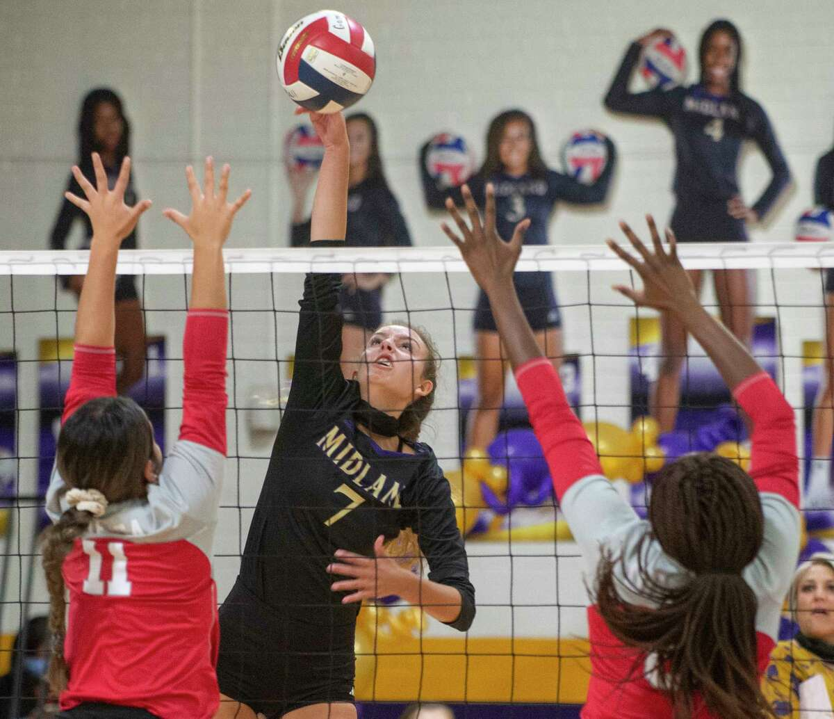 Midland High's Olivia Hale goes up for the hit as Odessa High's Kaia Minjarez and Julisha Terry try to block 09/29/2020 at the Midland High gym. Tim Fischer/Reporter-Telegram