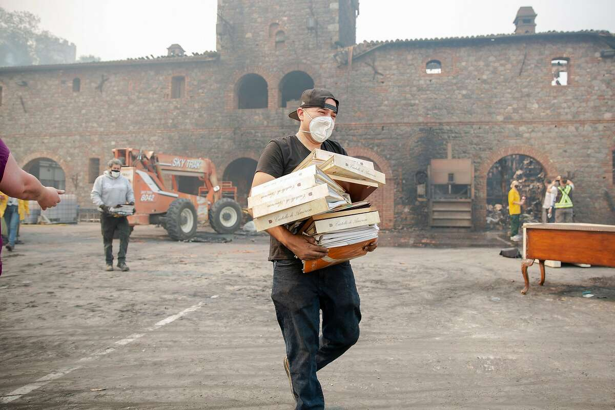 A worker carries out binders of paperwork from the burned farmhouse at Castello di Amorosa during the Glass Fire in Calistoga, Calif. on Tuesday, Sept. 29, 2020.