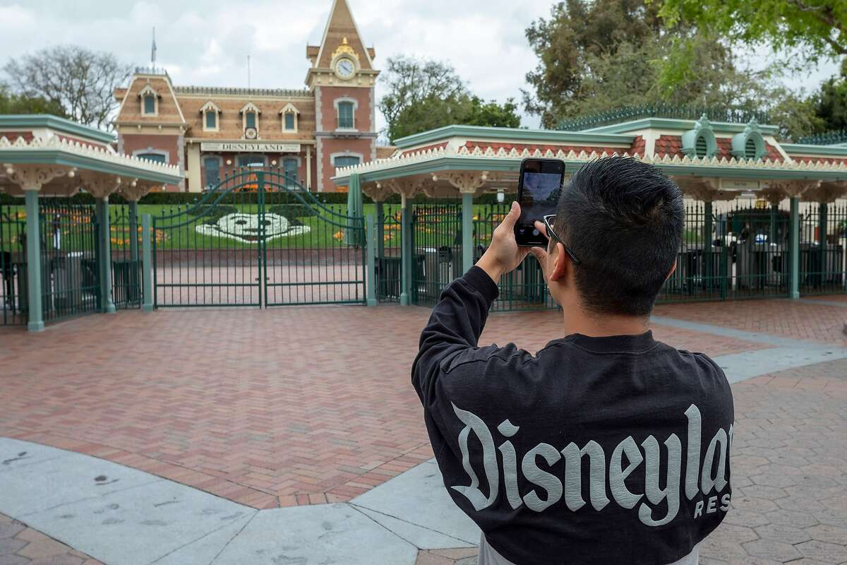 In this file photo taken on March 14, 2020 a man takes a photo outside the gates of Disneyland Park on the first day of the closure of Disneyland and Disney California Adventure theme parks.