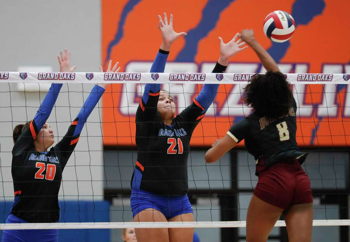 Grand Oaks outside hitter Fallon Thompson (21) tries to block a shot by Summer Creek right side hitter Kaitlyn Honora (8) beside middle blocker Kailee Blanchard (20) during a non-district high school volleyball match at Grand Oaks High School, Tuesday, Sept. 29, 2020, in Spring.