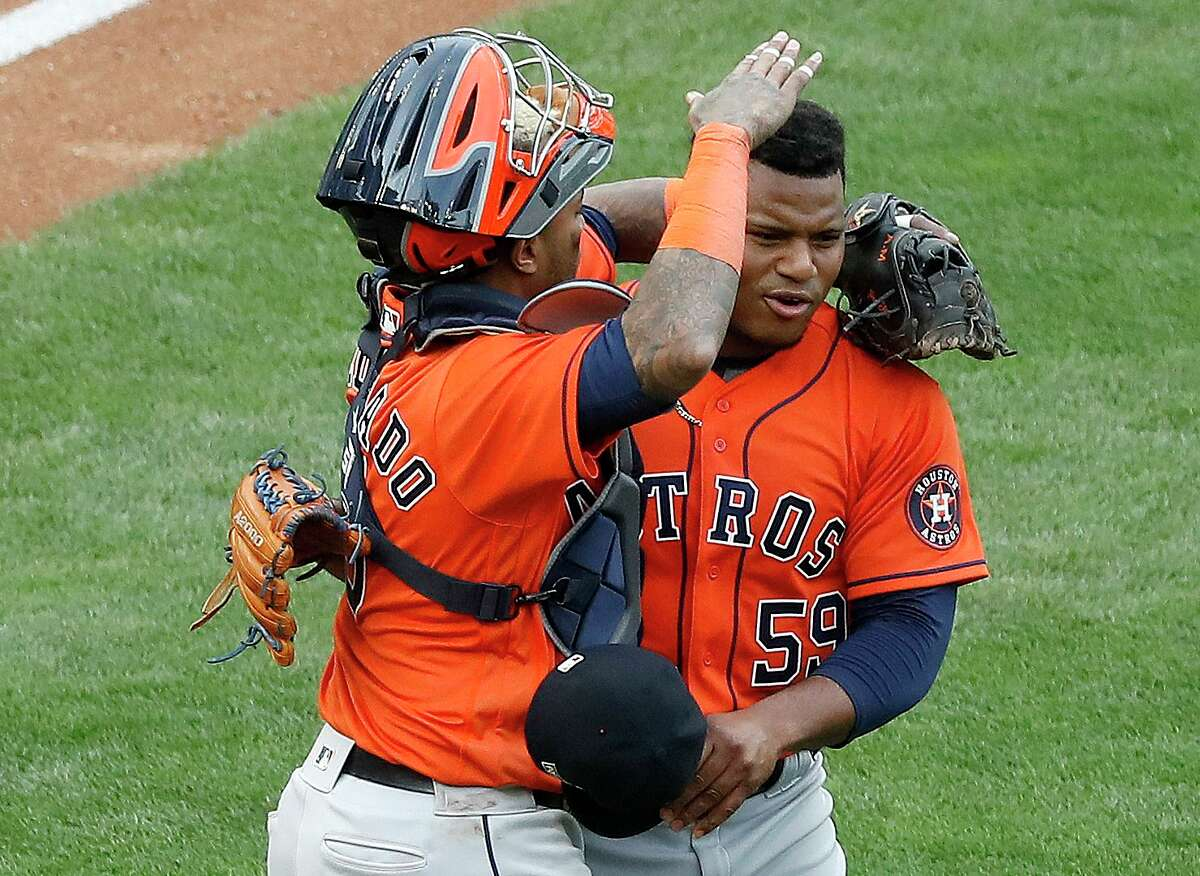 Catcher Martin Maldonado, left, celebrates the Astros' Game 1 victory with Framber Valdez, who threw five scoreless innings and escaped a two-on jam in the ninth with a game-ending double play.