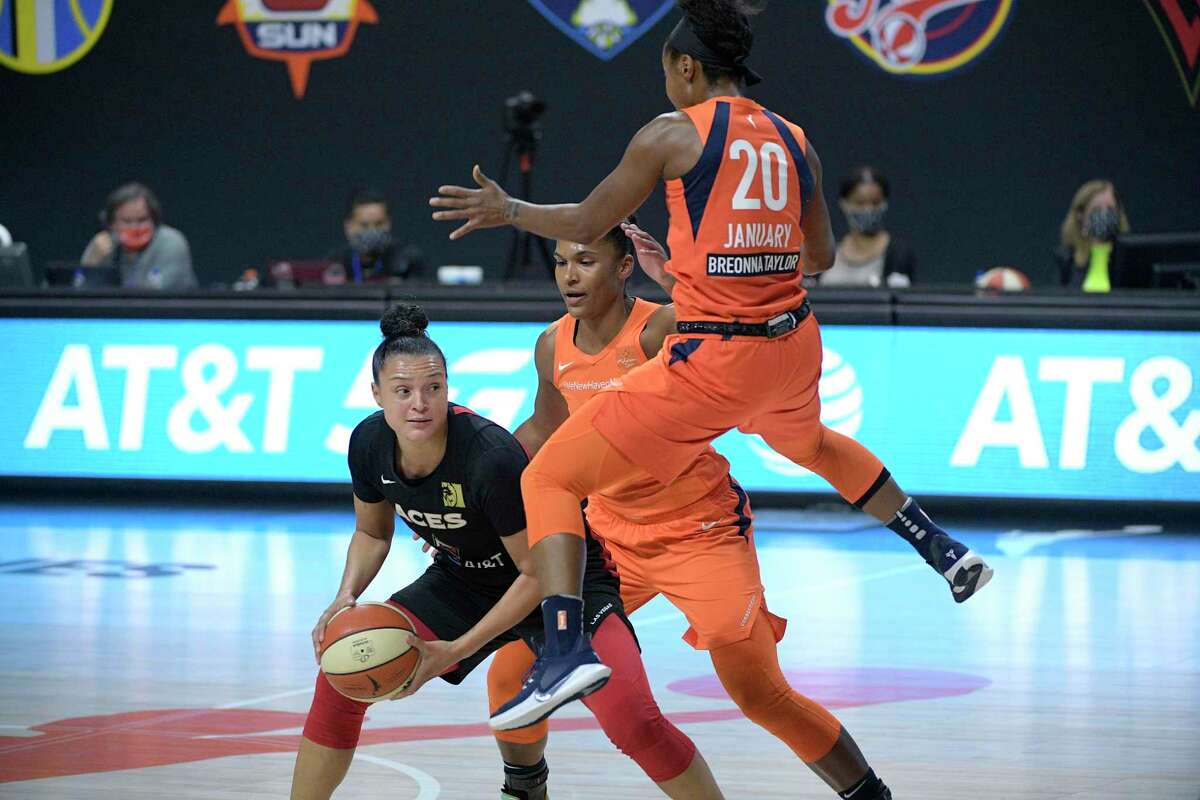 Las Vegas Aces guard Kayla McBride looks to pass the ball while defended by Connecticut Sun forward Alyssa Thomas (25) and guard Briann January (20) during the first half of Game 5 of a WNBA basketball semifinal round playoff series, Tuesday, Sept. 29, 2020, in Bradenton, Fla. (AP Photo/Phelan M. Ebenhack)