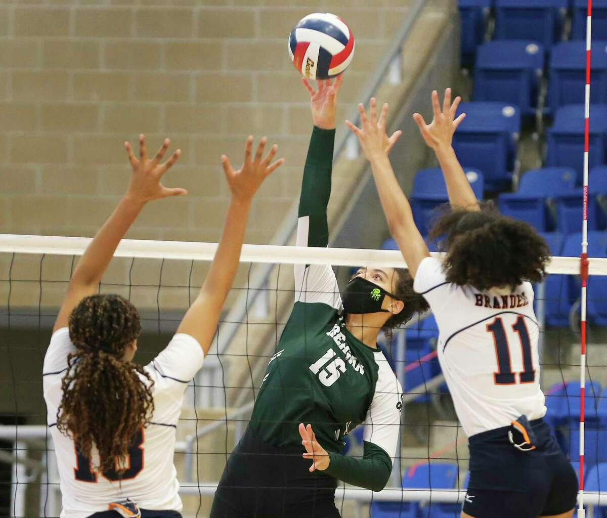 Reagan's Nyah Anderson (15) tips a shot over Brandeis' Austin Smoak (18) and Leila Smalls (11) during their girls volleyball game at Northside Sports Gym on Tuesday, Sept. 29, 2020. The Broncos defeated the Rattlers, 4-1, to take the contest.