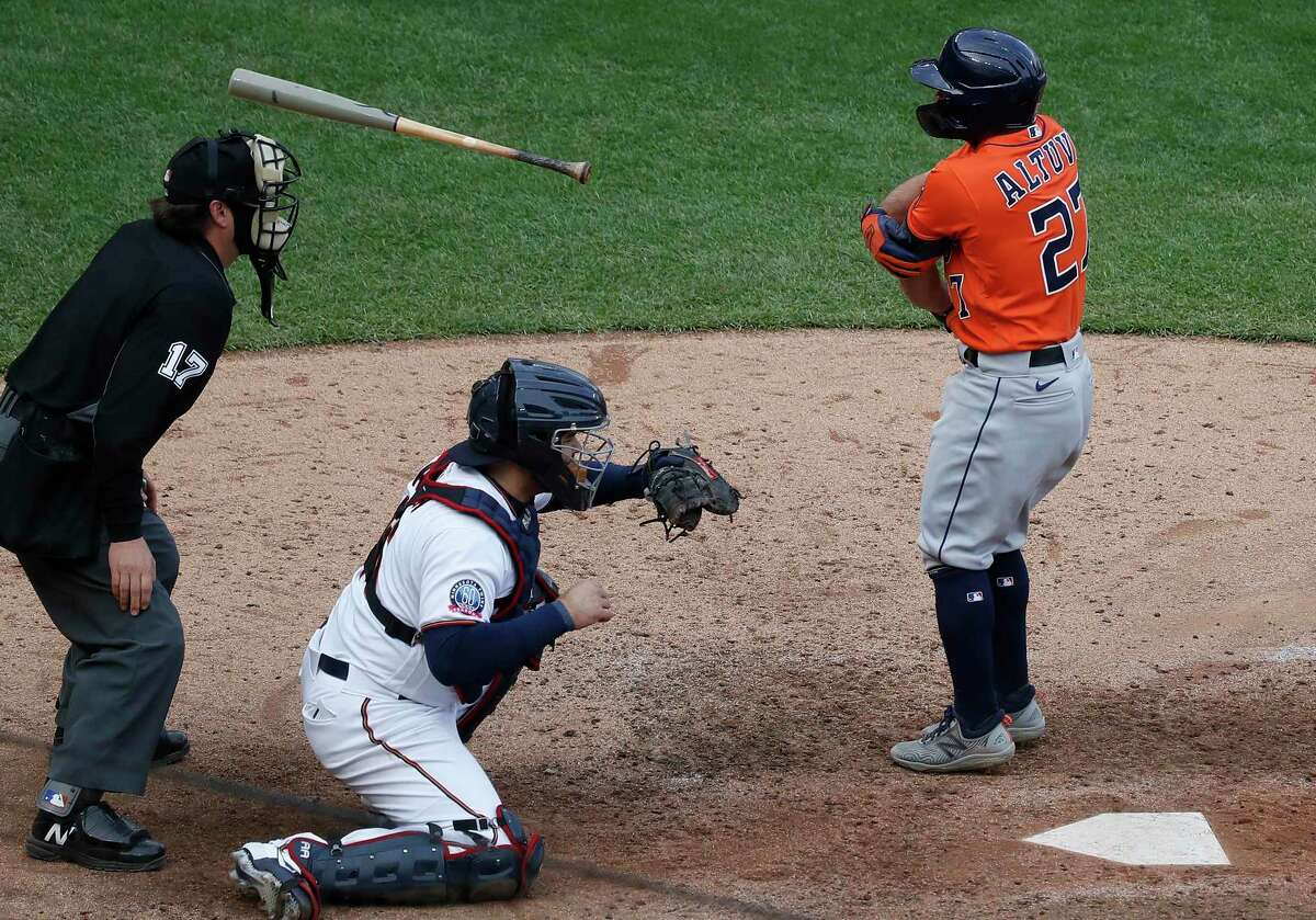 Jose Altuve, right, tosses his bat after being walked by Twins reliever Sergio Romo to force in the go-ahead run in Tuesday's 4-1 Astros victory.