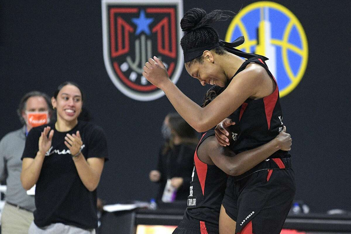 Las Vegas Aces center A'ja Wilson, right, and guard Sugar Rodgers celebrate after getting the win over the Connecticut Sun in Game 5 of a WNBA basketball semifinal round playoff series, Tuesday, Sept. 29, 2020, in Bradenton, Fla. (AP Photo/Phelan M. Ebenhack)