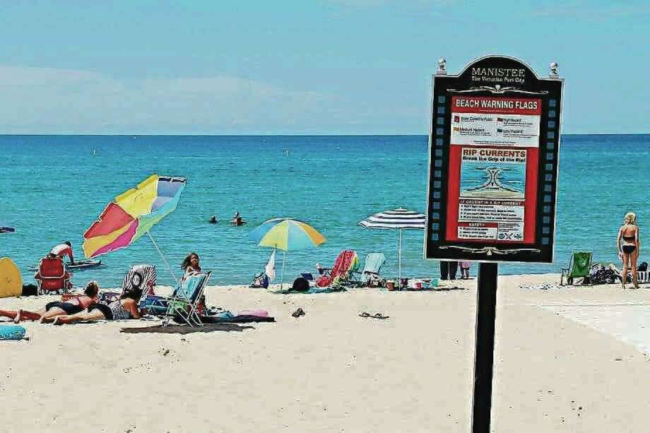 A sign at First Street Beach in Manistee warns of possible rip currents, as well as explaining the meaning of the beach warning flags that can be found at First Street Beach and Fifth Avenue Beach. (File photo)