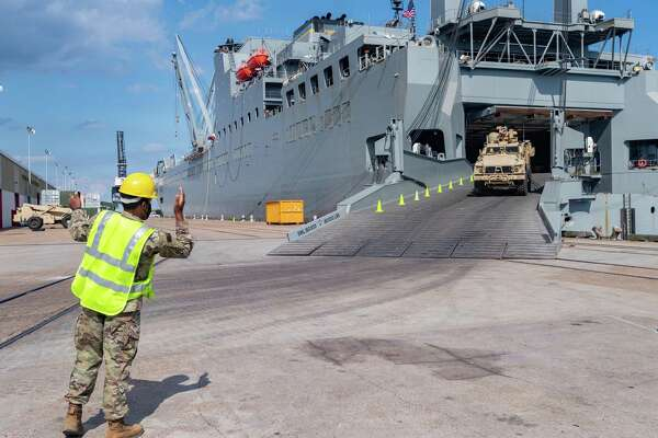 """A soldier directs a vehicle disembarking from the USNS Frazier. If you're seeing a lot of soldiers and Army vehicles, on the streets of Port Arthur, do not be alarmed. About a thousand soldiers of The 7th Transportation Brigade (Expeditionary) of the US Army also known as the """"Army's Navy"""" are unloading hundreds of vehicles, shipping containers, and helicopters from the US Naval Ship Frazier, staging them at the port. The equipment is being transferred from the 2nd Brigade Combat Team, 25th Infantry Division, Schofield Barracks, Hawaii to Fort Polk in Louisiana. The 7th Transportation Brigade, Joint Base Langley-Eustis, VA were called for a readiness exercise on August 12, 2020 to test their ability to alert, recall, and deploy the 2nd Infantry Brigade Combat Team, 25th Infantry Division under emergency conditions. Photo made on September 26, 2020. Fran Ruchalski/The Enterprise"""