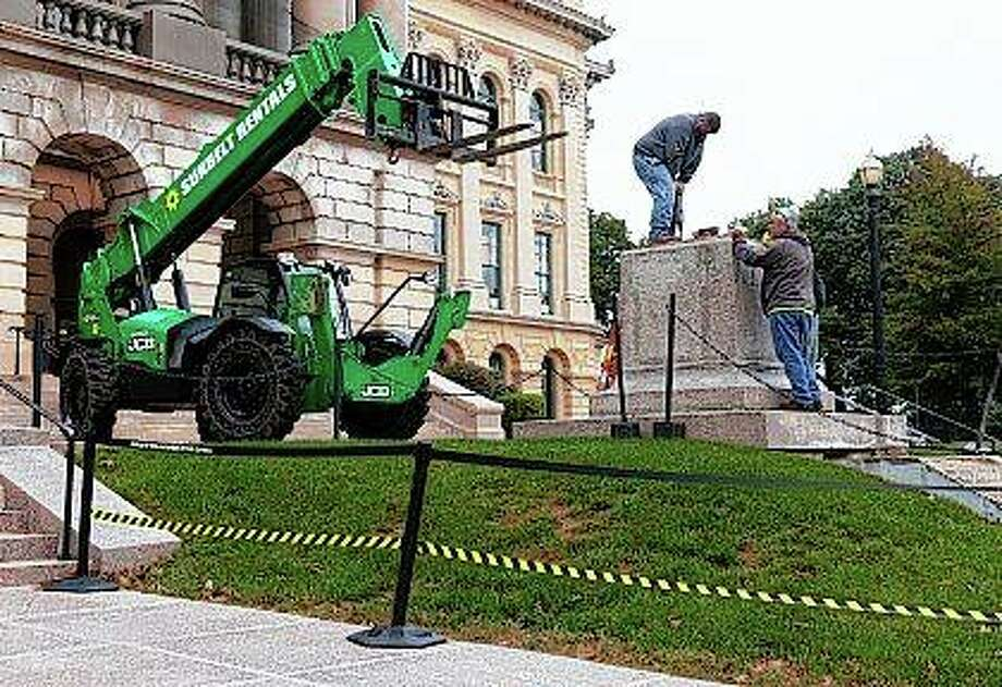 Crews work Monday to mount a plate on top of the pedestal where a statue of Stephen A. Douglas, a 19th century senator from Illinois who owned slaves and was a longtime nemesis of Abraham Lincoln, stood outside the Illinois State Capitol. The statue was removed on Saturday. Photo: Justin L. Fowler | The State Journal-Register Via AP